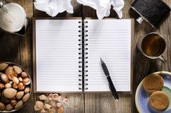 Ein offenes Notizbuch mit Leerseiten, Stift auf hölzerner Tabelle Tasse Tee, Hüftenflasche, Nüsse und Kekssnack Stockfotografie