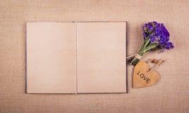 Ein offenes Tagebuch mit leeren Seiten, ein Blumenstrauß von trockenen Wildflowers und ein Herz des Holzes Kopieren Sie Platz Stockfotografie