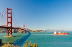 Ein orange Containerschiff mit den Kränen, die unter das goldene GA überschreiten Lizenzfreies Stockbild