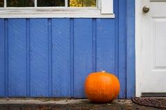 Ein orange Kürbis auf der Eingangsterrasse eines purpurroten Hauses Stockfotografie