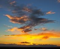 Ein orange Sonnenuntergang an einem bewölkten Tag Stockbild