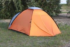 Ein orange Zelt an einem Picknick im Wald auf dem Sand mit dem Gras Stockbild