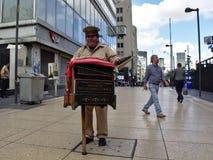 Ein organillero spielt Musik, wie er von den Spitzen mit seinem Hut fragt stockbild
