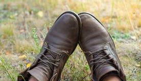 Ein Paar abgenutzte braune Lederschuhe über dem Landschaftshintergrund Lizenzfreie Stockfotos