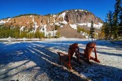 Ein paar Adirondack-Stühle, die im Frühjahr Wartewärmeres Wetter des Schnees sitzen Stockbild
