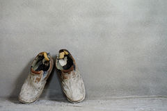 Ein Paar alte Schuhe auf Zementhintergrund, alter Hintergrund, alte Stiefel Lizenzfreies Stockbild