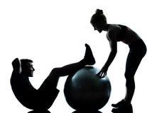 Ein Paar bemannen die Frau, die Trainingseignung ausübt Stockfotografie