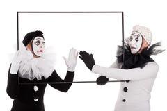 Zwei Clowne, die ein leeres Bild säubern Stockfotografie
