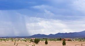 Ein Paar Blitzschläge über einer ländlichen Nachbarschaft Lizenzfreies Stockbild