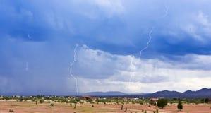 Ein Paar Blitzschläge über einer ländlichen Nachbarschaft Lizenzfreies Stockfoto