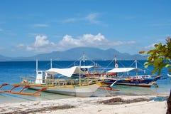 Ein Paar Boote sitzen im haarscharfen blauen Wasser vor der Küste der Philippinen mit herrlichen Bergen und blauem Himmel lizenzfreies stockfoto