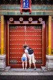 Ein Paar, das durch die kleine Öffnung in einer Tür in der Verbotenen Stadt in Peking China späht lizenzfreie stockfotografie