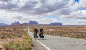 Ein Paar, das durch Monument-Tal radfährt Lizenzfreies Stockbild