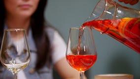 Ein Paar, das durch Tabelle in einem Café sitzt Ein Mann gießt das Getränk im Glas stock footage