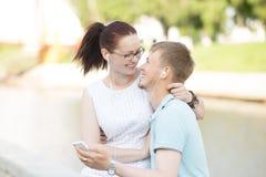Ein Paar, das im Park sitzt und Musik am Telefon hört Lizenzfreie Stockfotos