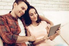 Ein Paar, das ein Tablet an Valentinsgruß ` s Tag aufpasst stockfotos