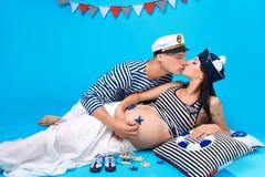 Ein Paar, das während der Schwangerschaft küßt Stockfotografie