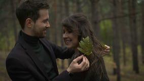 Ein Paar in der Liebe im Wald an der Dämmerung Junger Mann seine Freundin umarmend und mit ihrem Haar gespielt Er trug a stock video footage