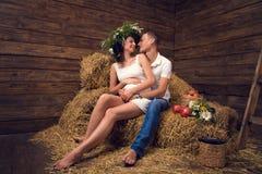 Ein Paar in der Liebe während der Schwangerschaft im Hayloft Stockbild