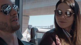 Ein Paar in der Sonnenbrille, die in einem beweglichen Bus und in einer Unterhaltung sitzt stock video footage