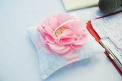 Ein Paar Eheringe auf geformtem Kissen der Blume lizenzfreie stockbilder
