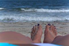 Ein Paar Füße den Ozean gegenüberstellend Stockbilder