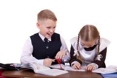 Ein paar Grundschüler sitzen an einem Schreibtisch Lizenzfreies Stockbild