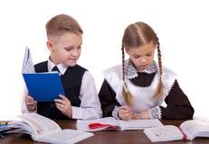 Ein paar Grundschüler sitzen an einem Schreibtisch Lizenzfreies Stockfoto