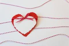Ein Paar heftige Papierherzen gebunden mit einem roten und weißen Band mit gewellten Linien anderer Bänder Stockbilder