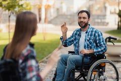Ein paar invalids auf Rollstühlen trafen sich im Park Ein Mann grüßt eine Frau Stockfotos