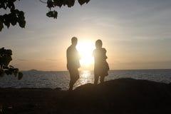 Ein Paar Liebhaber sehen einen Seesonnenweg mit weitem Schiff und Blättern Stockbilder