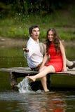 Ein Paar Liebhaberleute sitzen auf der Brücke Lizenzfreies Stockbild