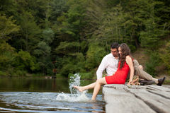 Ein Paar Liebhaberleute sitzen auf der Brücke Stockfotografie