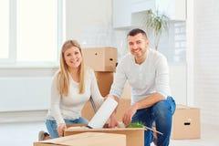 Ein Paar mit Kästen bewegt sich auf ein neues Haus lizenzfreie stockfotografie
