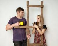 Ein Paar mit Schalen steht während der Reparatur nahe einer hölzernen Co still Stockfotos