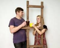 Ein Paar mit Schalen steht während der Reparatur nahe einer hölzernen Co still Stockfoto