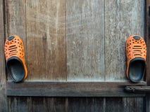 Ein Paar orange Gummipantoffel auf altem hölzernem Lizenzfreie Stockbilder