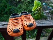 Ein Paar orange Gummipantoffel auf altem hölzernem Lizenzfreie Stockfotografie