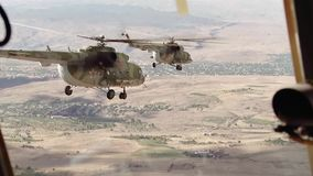 Ein paar russische Hubschrauber fliegen über das Dorf zwischen den Bergen stock video footage