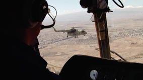 Ein paar russische Militärhubschrauber fliegen auf einer Mission zwischen den Bergen stock video footage