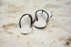 Ein Paar Sandalen oder Flipflops der Frau auf natürlichem weißem Strand Lizenzfreies Stockfoto