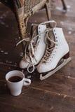 Ein Paar Schlittschuhe mit der Tasse Tee stehend auf dem Boden Stockbild