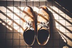 Ein Paar Schuhe unter einem Muster des Schattens Stockfoto