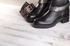 Ein Paar schwarze Lederstiefel mit Gurt Lizenzfreie Stockbilder