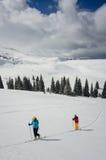 Ein paar Skifahrer, die einer Bahn im Schnee folgen Stockbilder