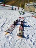 ein Paar Skis gelassen auf dem weißen Schnee mit niemandem, das sie auf einer Ski fahrenden Szene am Hintergrund in einem sonnige lizenzfreies stockfoto