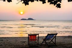 Ein paar Sonnenruhesessel auf dem Strand während des überraschenden Sonnenuntergangs relax lizenzfreie stockfotos