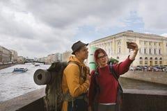 Ein paar Touristen, die selfies vor dem hintergrund der Architektur nehmen Lizenzfreies Stockfoto