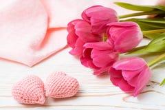 Ein Paar von gestrickten rosa Herzen und von Blumenstrauß von frischen Tulpen auf einem Holztisch Stockbild