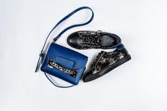 Ein Paar von schwarzen ledernen Turnschuhen mit silbernen Sternen und von blauen Tasche mit einer Goldkette auf einem wei?en Hint lizenzfreie stockfotografie